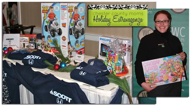 Guest Blogger, Jennifer Worthington Lower stands with her Toys for Tots donation for the Holiday Extravaganza. On the left is the Scott Honda Raffle table highlighted by the Buzz Lightyear Power Wheels.